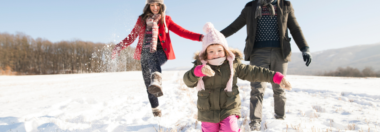 Family enjoying the winter playing in the snow