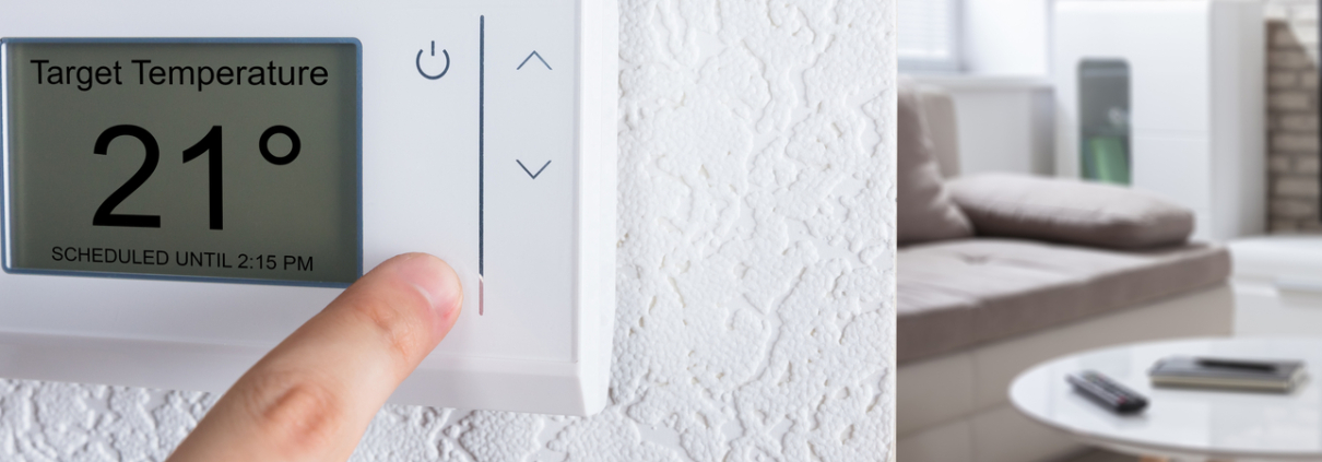person adjusting their thermostat