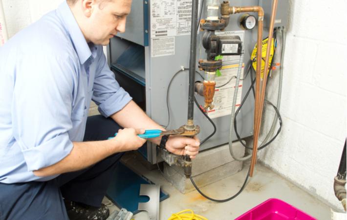 repair man fixing a gas furnace