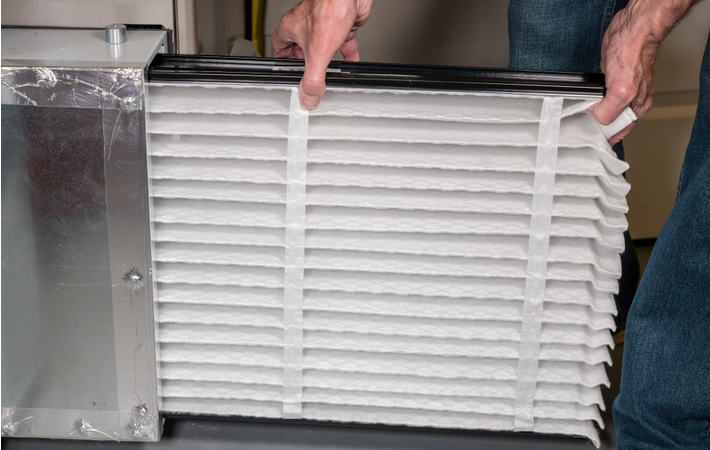 man inserting a new filter into his furnace