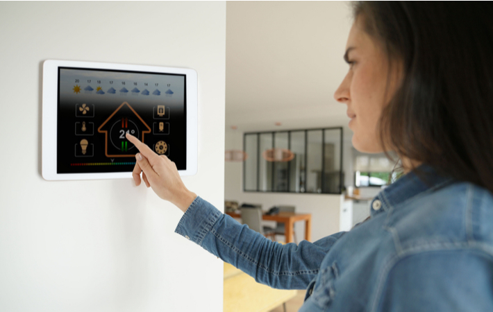 woman using the touchscreen on an advanced thermostat